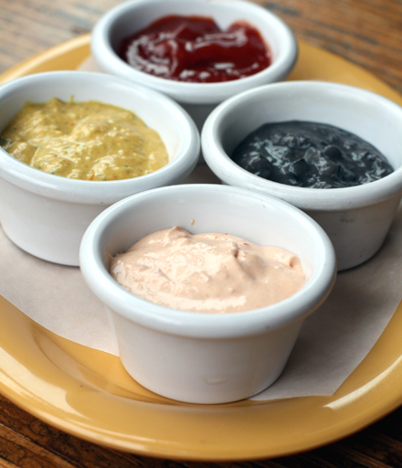 Clockwise from top: Spiced Ketchup, Black Bean Paste, Spicy Cream and Pica'Pun signature hot sauce.