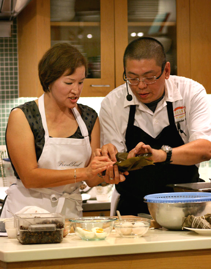 Chef Alex Ong of Betelnut teaching me how to fold a joong rice tamale at Macy's. (Photo by Ben Seto)