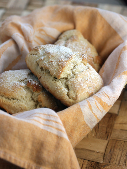A basket of warm scones full of sweet marzipan nubbins.