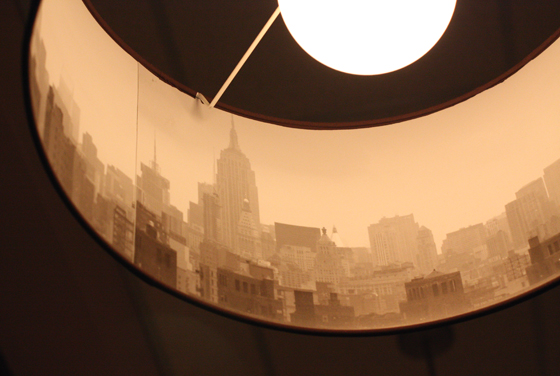 Drum lights hang over tables and hide a cityscape of New York.