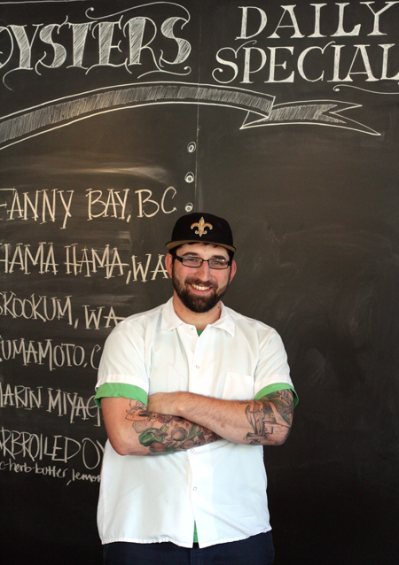 Chef Justin Simoneaux stand in front of the specials board at the Boxing Room in San Francisco.