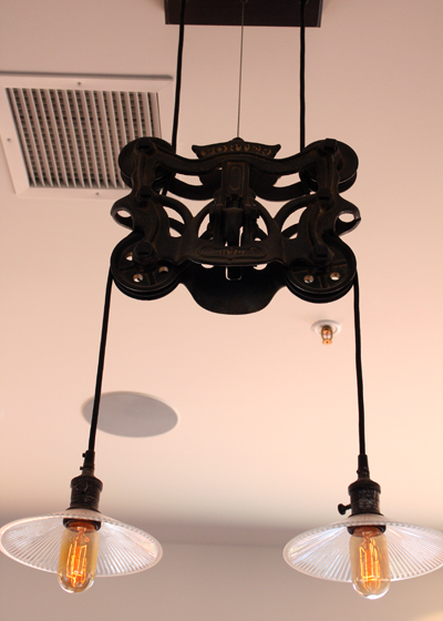 Cool light fixtures fashioned with iron pulleys.