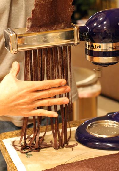 Cutting strands of fettuccini.