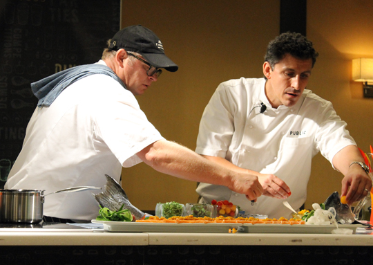 Chefs Al Brown and Brad Farmerie putting the garnishes on their dramatic plate.