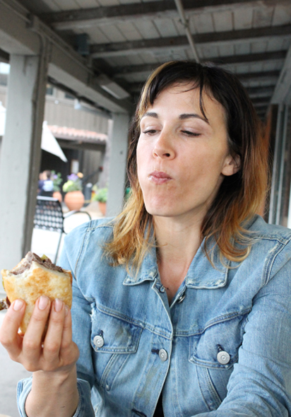 Anya Fernald being a good sport by letting me snap a pic when she took a bite of the Philly cheesesteak.