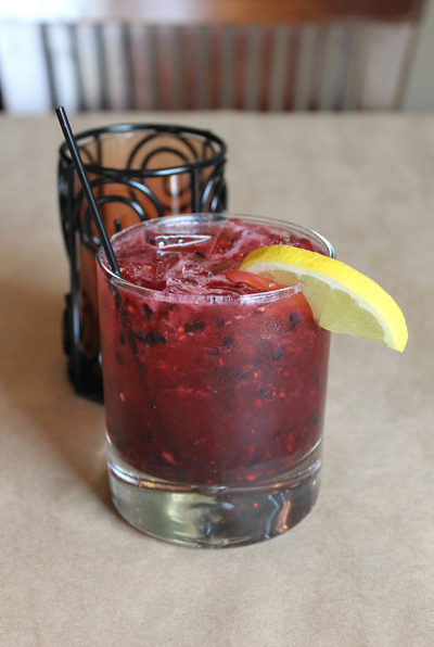 A cocktail made with fresh blackberries.
