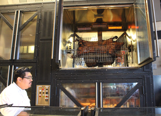 A whole pig cooking in an elaborate grill.