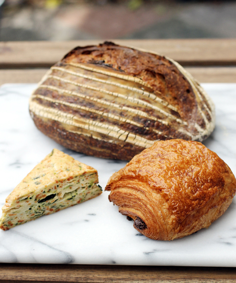 A selection of Manresa Bread specialties: levain (back), kale scone (front left), and chocolate croissant (front right).