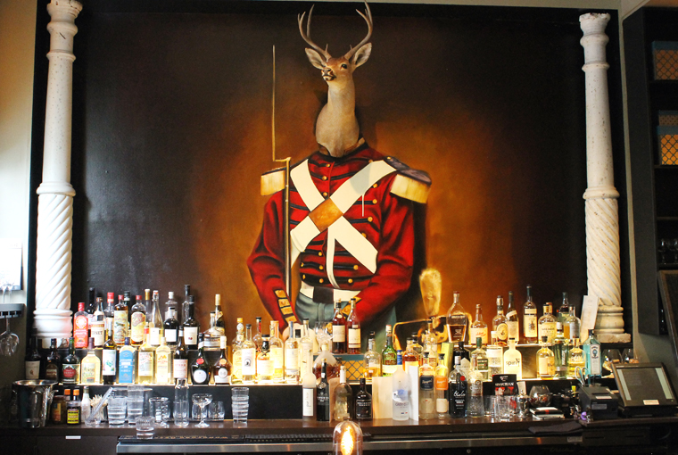 The deer painting still stands sentry over the bar.