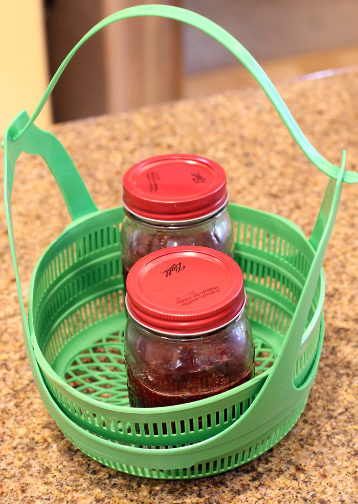 The filled jars arranged inside the canning basket.
