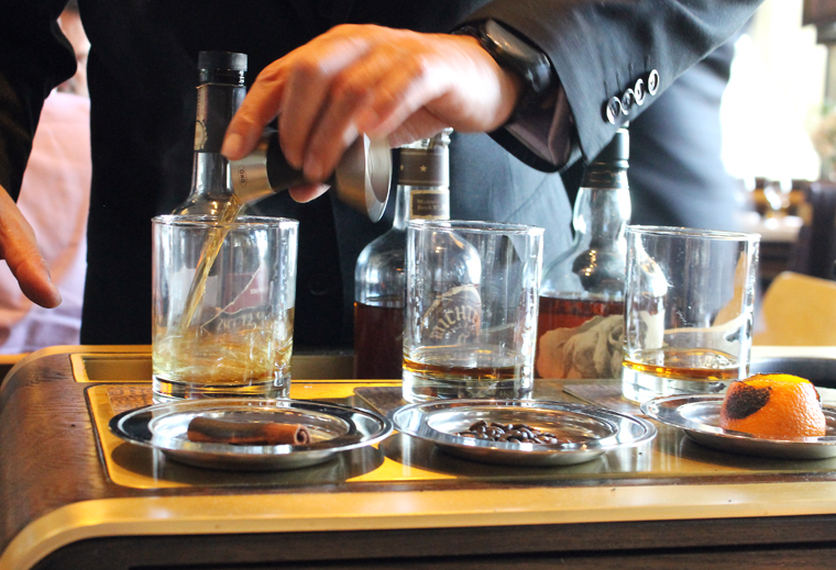 Filling each glass with one of three different bourbons.