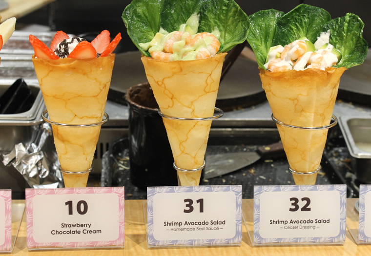 A display of sweet and savory crepes, wrapped up like cones so you can take it to-go easily.