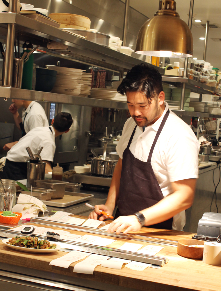 Chef Brandon Jew expediting in the kitchen of his Mister Jiu's.