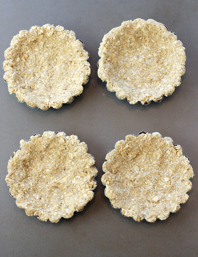 The dough is pressed into little tart pans before baking.