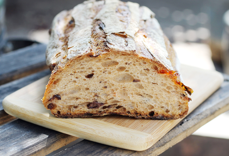 A proper loaf studded with olives and tomatoes.