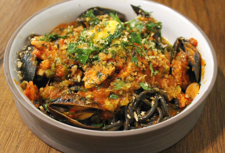 Squid ink pasta with a plethora of seafood and olives.