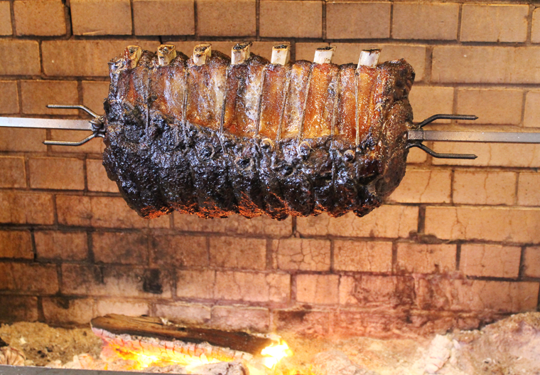 The rotisserie turns the prime rib over the flames.