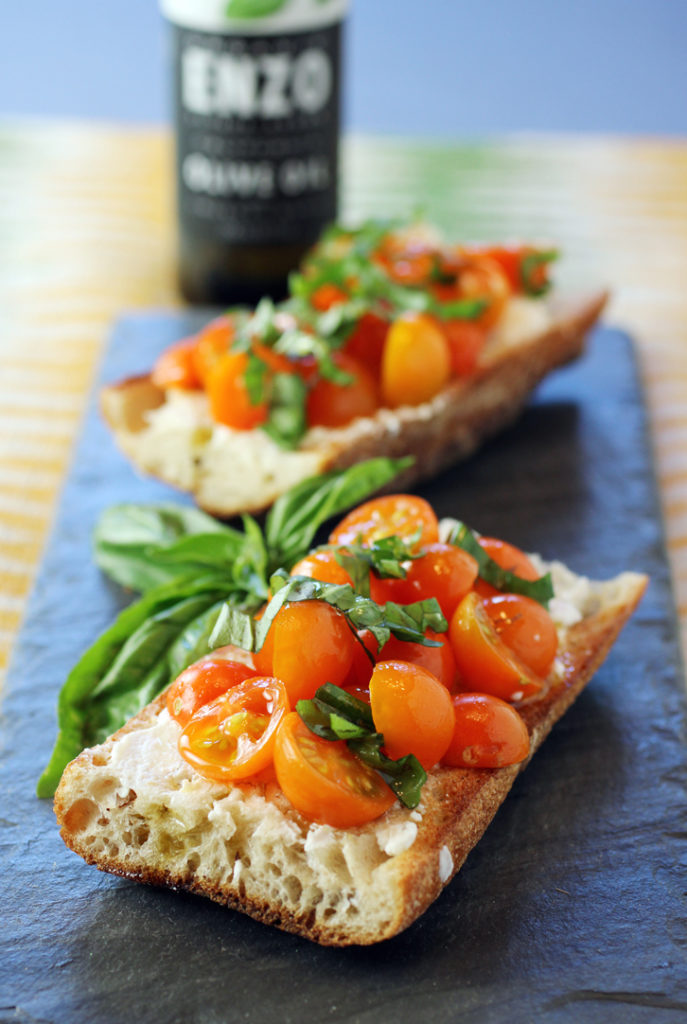 Toasted baguette topped with goat cheese, cherry tomatoes, basil, and a drizzle of Enzo Organic Basil Crush.