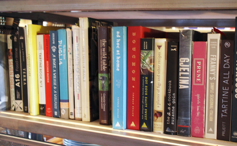 A collection of cookbooks underneath the main kitchen island, which guests can peruse