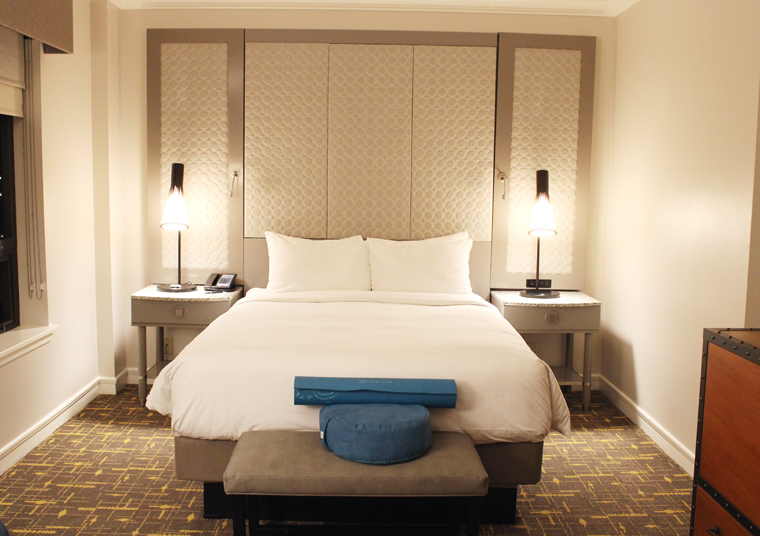 An Urban Sanctuary room, with a yoga mat at the foot of the bed.