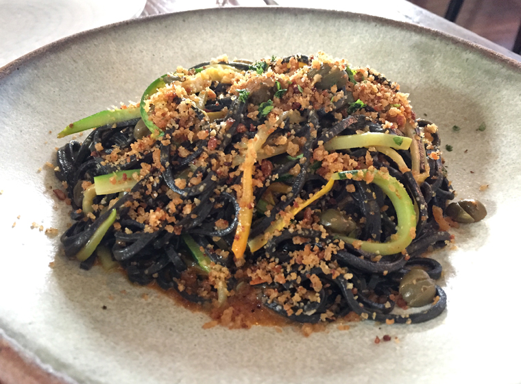 A tangle of squid ink pasta and strands of zucchini.