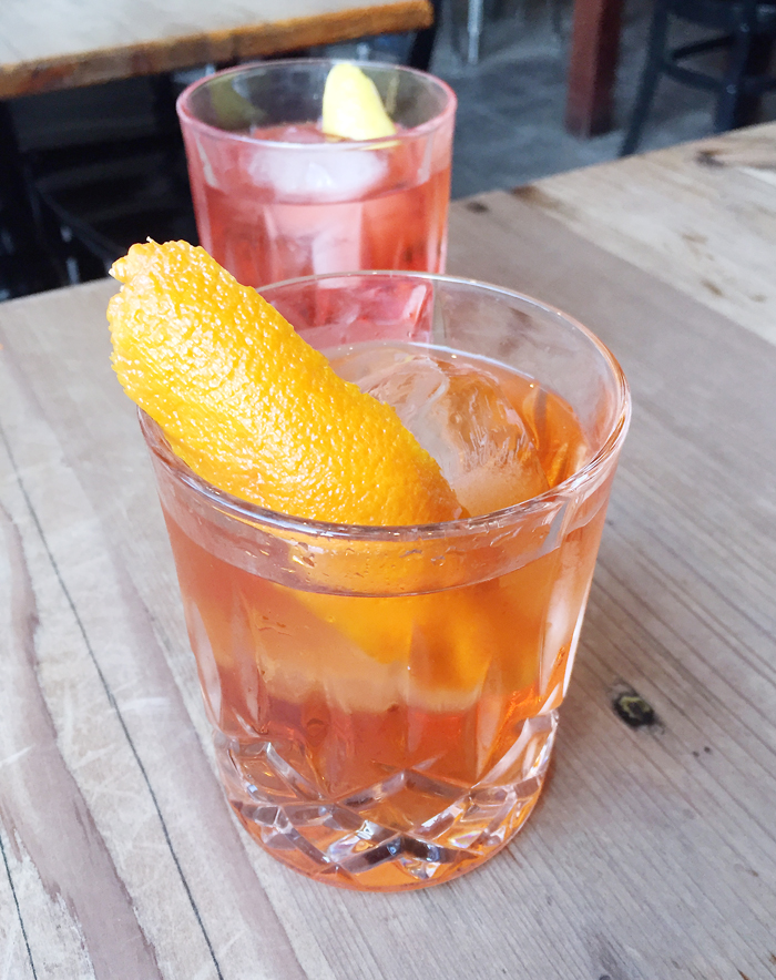 A classic Negroni (back), and a riff on one with major orange presence (front).
