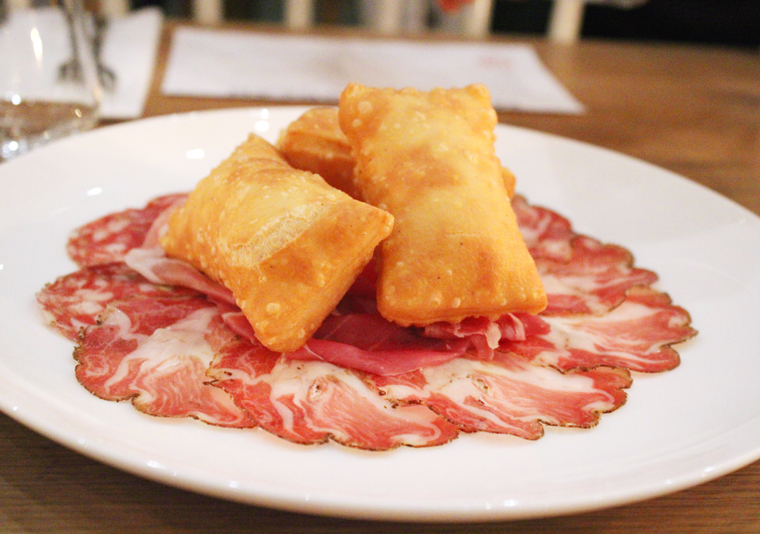 Paper-thin slices of salumi topped with fried bread.