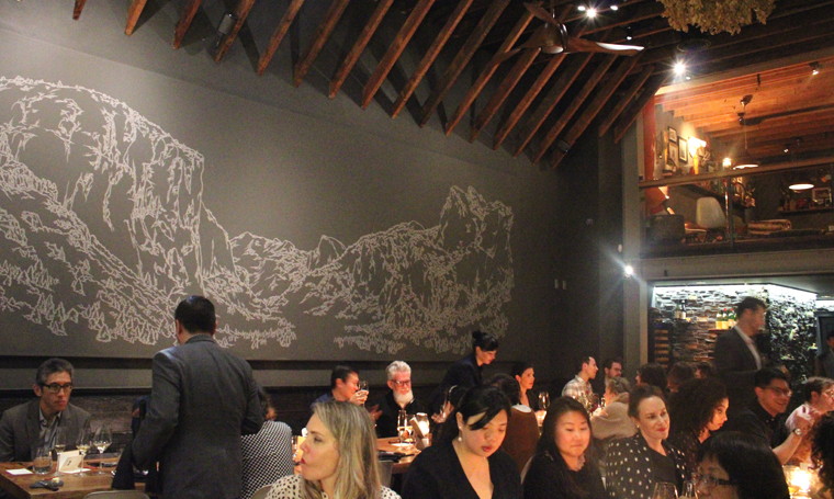 Guests fill up the two communal tables. A mural of Yosemite graces the wall.