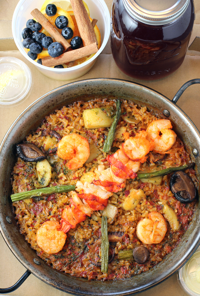 The restaurant's cooked, ready-to-eat lobster paella, packed to take home, along with sangria and garnishes.