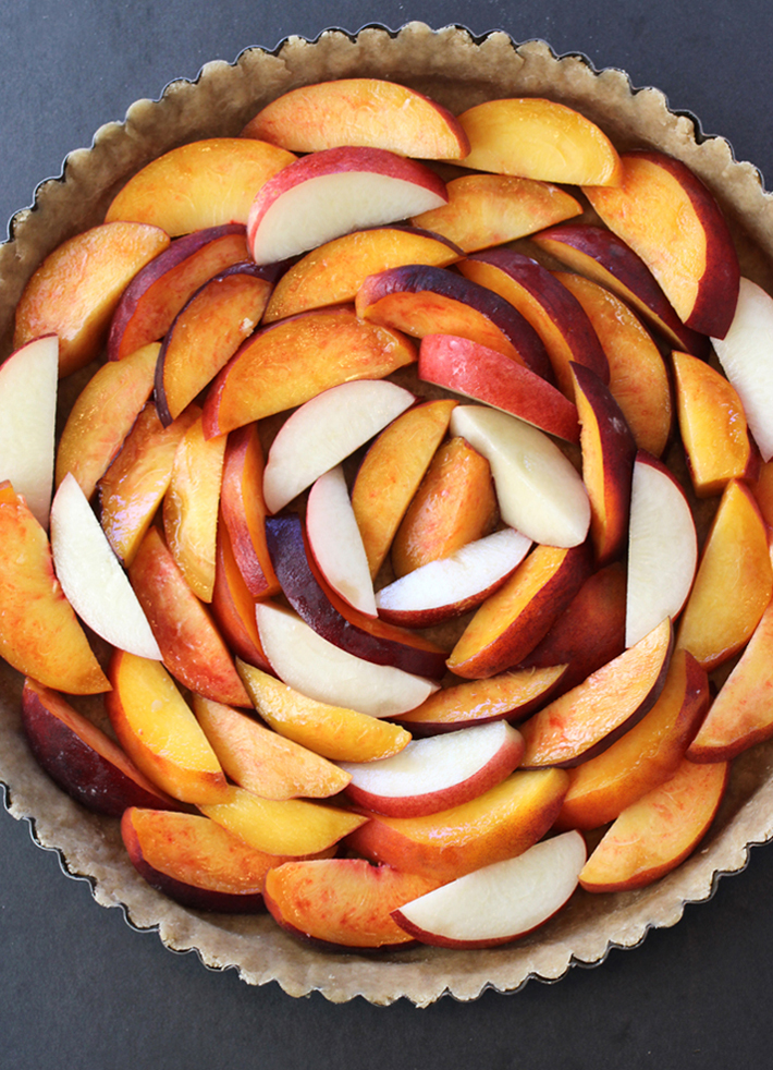 Peaches and one nectarine arranged in the crust before baking.