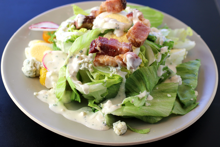 A wedge salad with big ham-like pieces of candied bacon.
