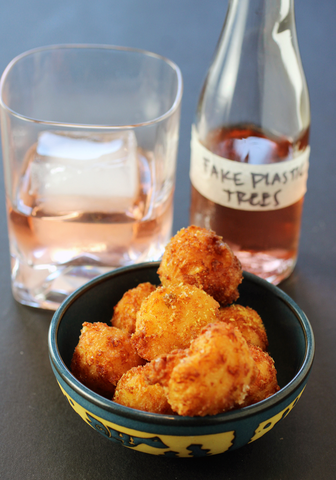 """Tiny, irresistible cheddar beignets alongside a to-go cocktail amusingly named, """"Fake Plastic Trees'' -- all from Braise."""