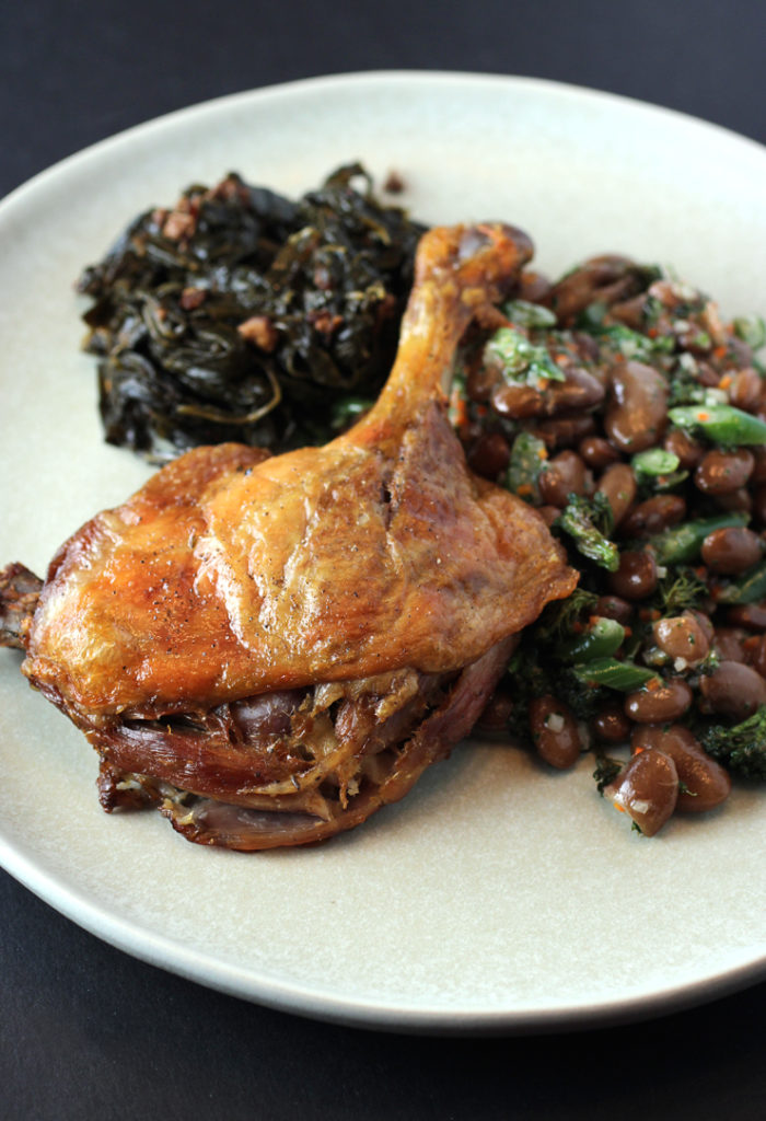 Duck leg confit with braised greens, and garlicky beans from Michelin-starred Protege.