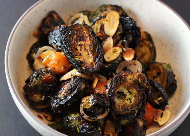 Charred Brussels sprouts with persimmon balls.