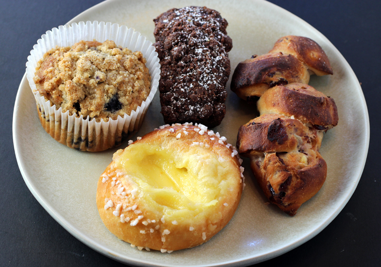 (Clockwise from top): Cocoa carrot cake, cranberry-orange epi, Meyer lemon brioche, and blueberry cornmeal muffin.