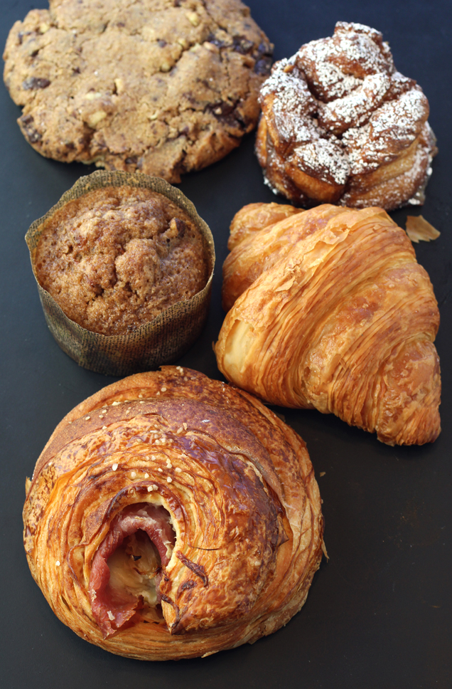 (Clockwise from top): Whole wheat chocolate chip cookie, monkey bread, croissant, pretzel ham & cheese croissant, and carrot muffin.