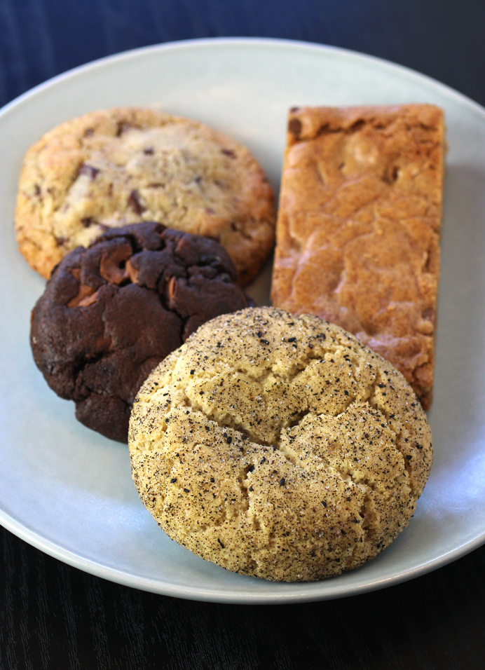 (Clockwise from top left): Tumaco dark chocolate almond cookie, peanut butter blondie, Earl Grey & Cardamom, and peanut butter chip chocolate cookies.
