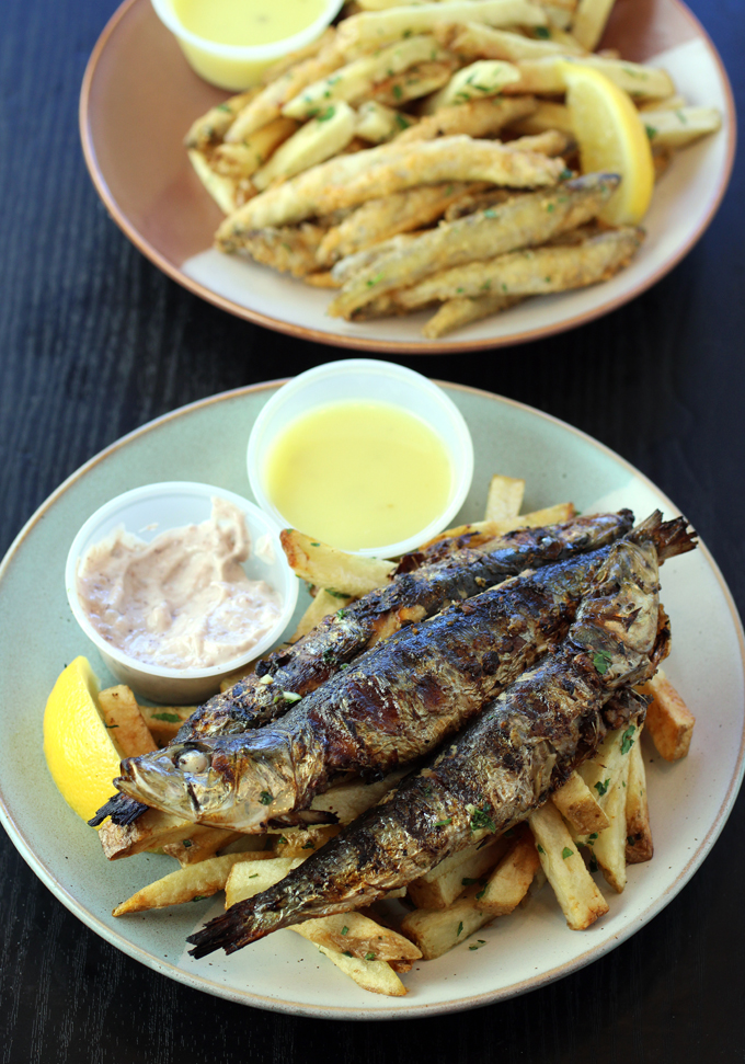 Fried smelt and fries (back), and grilled sardines with garlic fries (front).